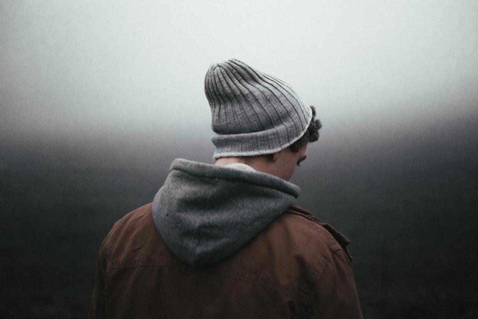 Man wearing wool hat and grey hoodie