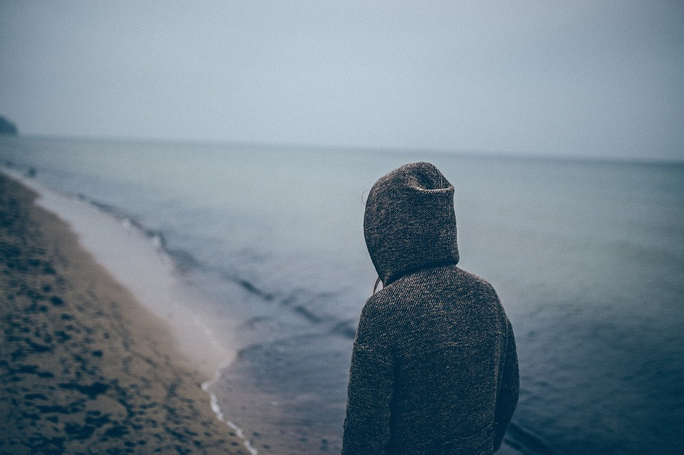 Woman wearing hoodie walking on beach