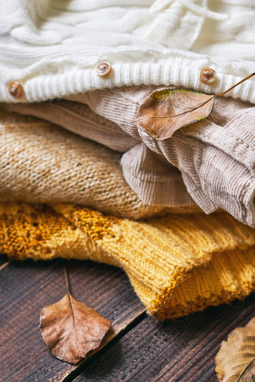 Stack of fall clothes for women on wooden background