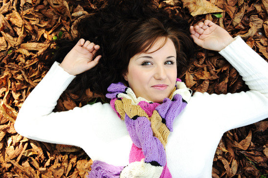 Young beauty girl laying on autumn ground and leaves, perfect face and natural skin, fashionable fall clothes