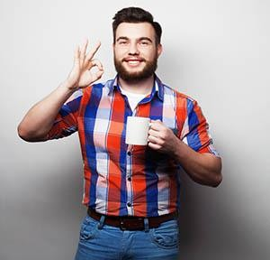 Young man smiling with coffee