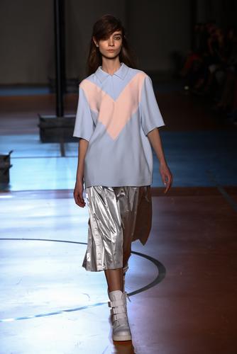 Model walking designer runway wearing pastel polo shirt