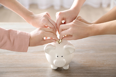 hands putting coins in piggy bank