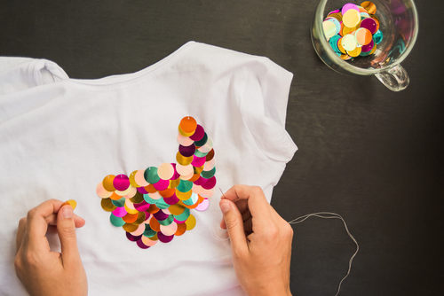 person decorates blank t-shirt sequins