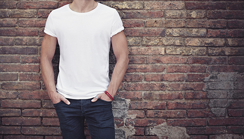 man wearing blank white t shirt brick wall