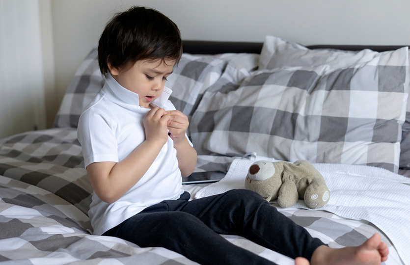 boy buttoning polo shirt