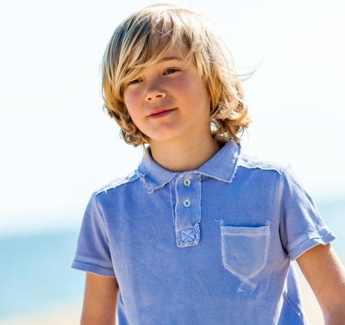 portrait of boy wearing worn polo shirt outdoors