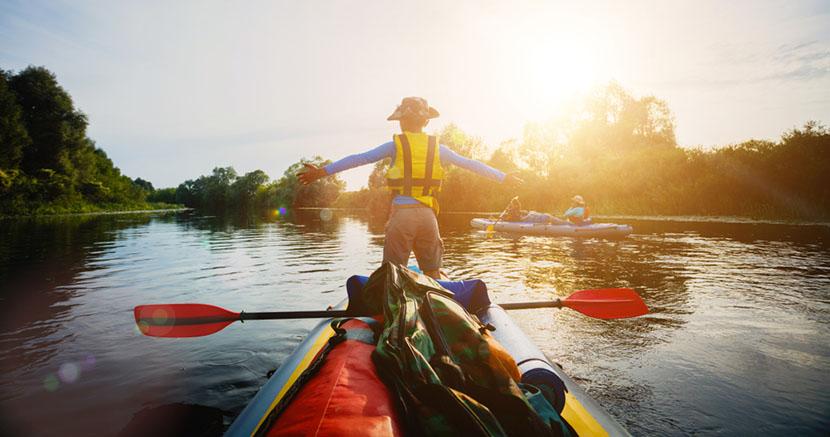 boy standing on kayak in lake