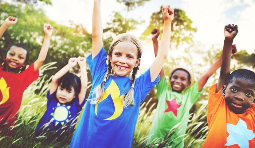 children cheering in grassy field