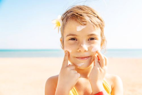 child putting sunscreen on face