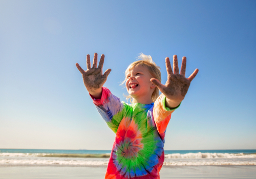 girl in tie dye shirt having fun at beach
