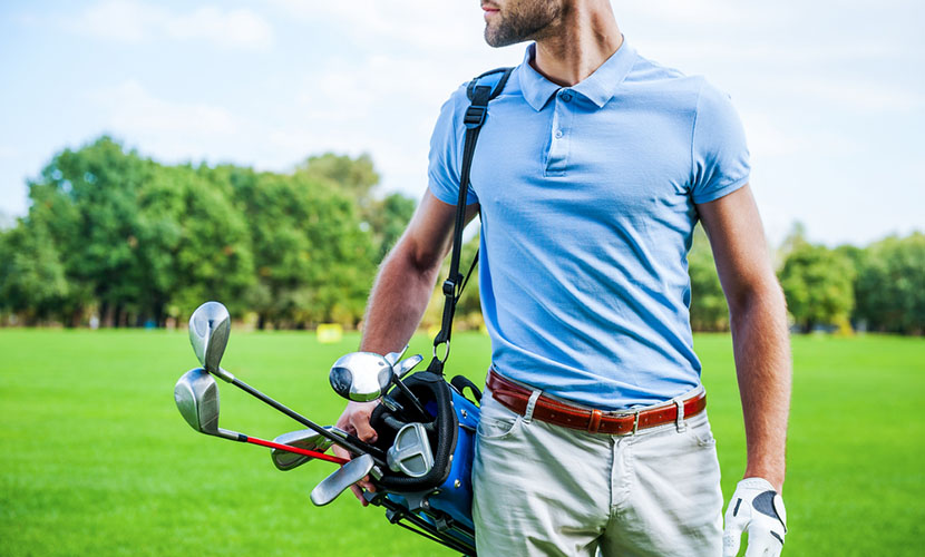 man wearing polo shirt carrying golf bag