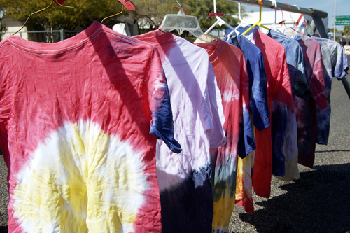 tie dyed shirts drying on hangers