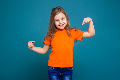 child pointing to her orange t shirt