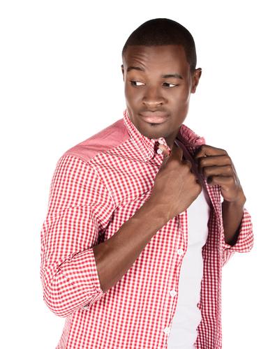 man buttoning up collared shirt
