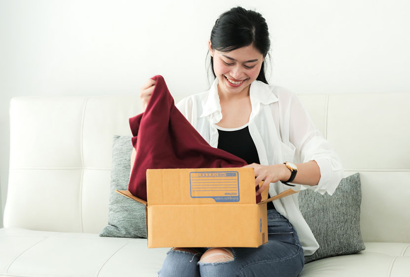 woman unpacking shirt from box
