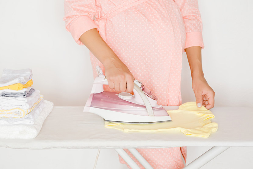 Pregnant woman in pink robe ironing