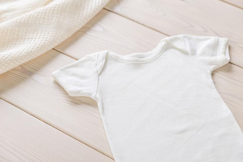 White baby shirt on wooden desktop