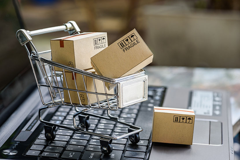 boxes in a small shopping cart on a laptop keyboard